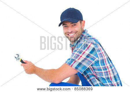 Portrait of happy handyman holding wrench on white background