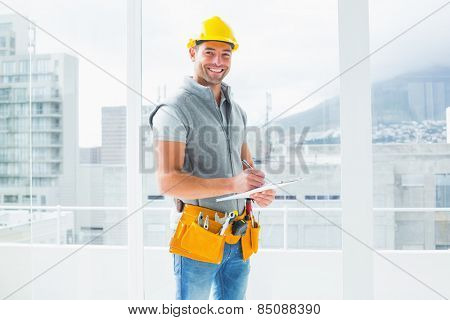 Portrait of smiling manual worker writing on clipboard in building