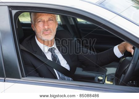 Thoughtful businessman in the drivers seat in his car