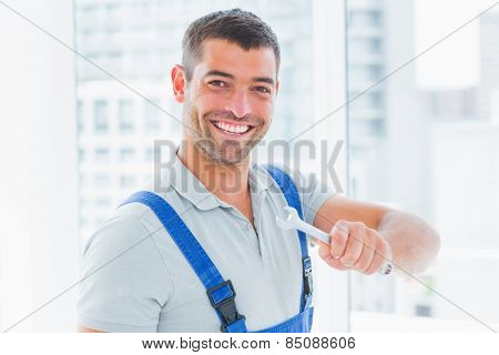 Portrait of smiling manual worker holding spanner in bright office