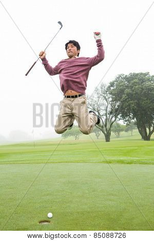 Excited golfer jumping up at the golf course