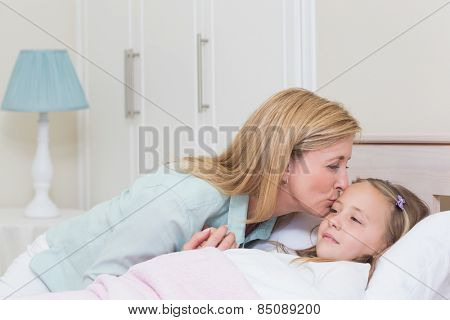 Mother kissing her daughter in the bedroom