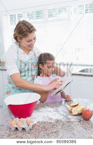 Mother and daughter baking together at home in kitchen