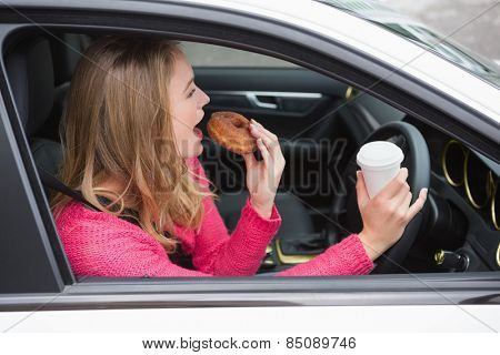 Young woman having coffee and doughnut in her car