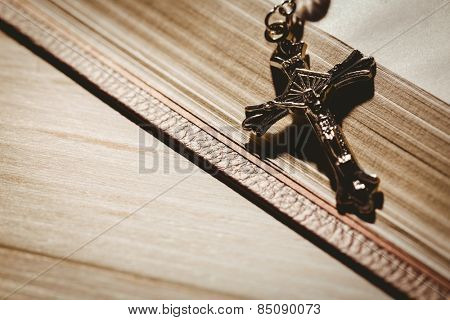 Open bible and silver crucifix on wooden table