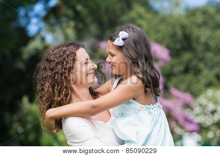 Happy mother and daughter smiling at each other in the garden