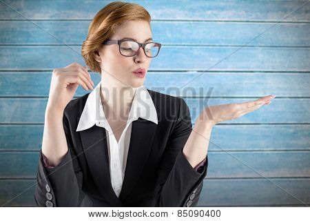 Businesswoman holding hand out in presentation against wooden planks