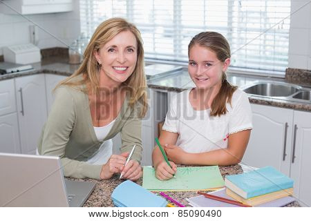 Happy mother helping daughter doing homework