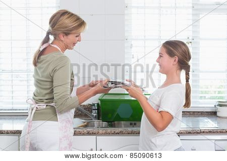 Mother and daughter recycling together at home in the kitchen