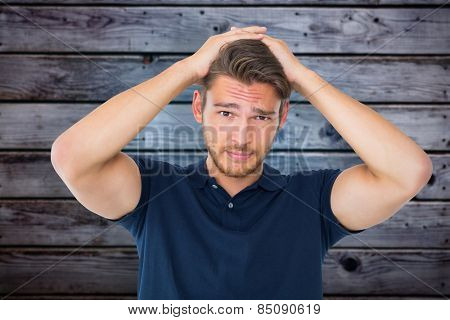 Handsome young man looking confused against grey wooden planks