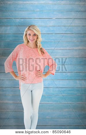 Pretty blonde smiling with hands on hips against wooden planks