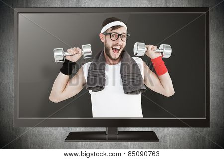 Geeky hipster lifting dumbbells in sportswear against blue background with vignette