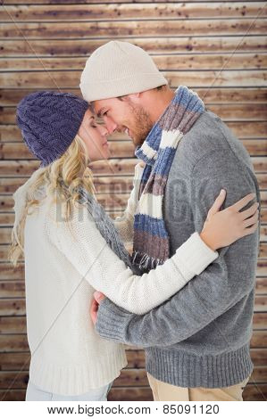 Attractive couple in winter fashion hugging against wooden planks
