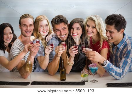 Friends with drinks against bleached wooden planks background