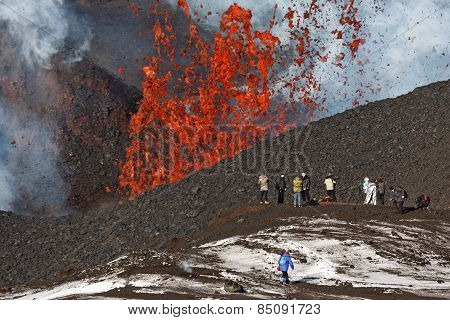 Eruption Tolbachik Volcano On Kamchatka, Tourists On Background Fountain Lava Escaping From Crater