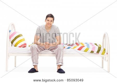 Cheerful young guy sitting on a bed isolated on white background