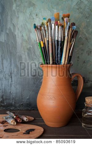Paintbrushes In A Jug From Potters Clay, Palette, Paint Tubes And Bottle Of Oil In Artist Studio.