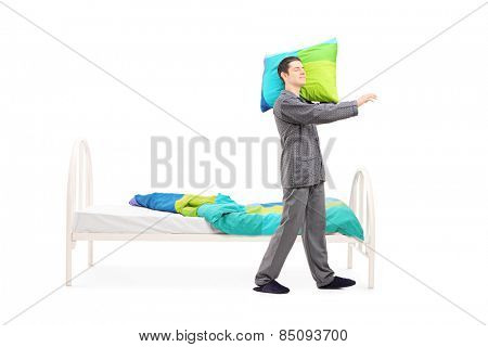 Full length portrait of a young man in pajamas sleepwalking by his bed isolated on white background