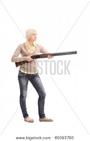 Full length portrait of a furious woman holding a shotgun isolated on white background