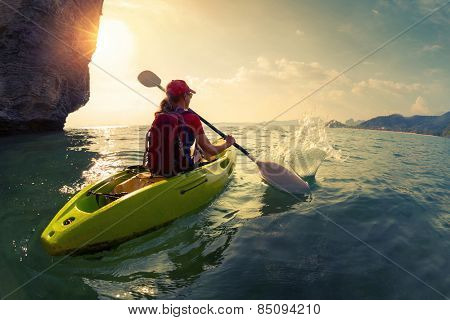Young lady paddling the kayak near the cliff at sunset