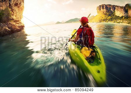 Young lady paddling the kayak in a bay with limestone mountains. Motion blurred water surface