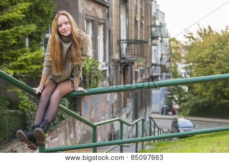 Young cute long-haired girl sitting on the parapet in the old town.