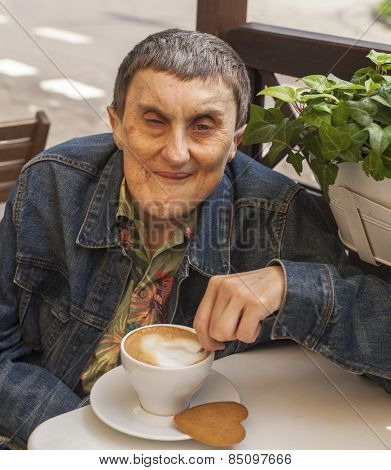 Disabled man with cerebral palsy sitting at outdoor cafe with a cup of coffee.