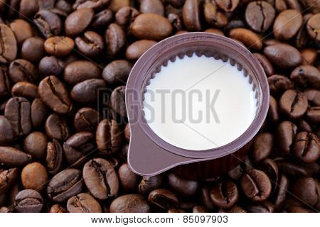 A small cup of Coffee Creamer on coffee beans