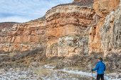 stock photo of collins  - senior male hiking in sandstone canyon in winter - JPG