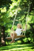 stock photo of swing  - Little smiling girl on a swing - JPG