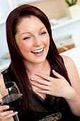 Delighted Woman Holding A Wine Of Glass At Home