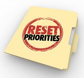 picture of reorder  - Reset Priorities words stamped on a manila folder to illustrate a change in the most important jobs or tasks to handle first in order - JPG