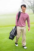 image of golf bag  - Golfer standing holding his golf bag smiling at camera at the golf course - JPG