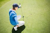 picture of ladies golf  - Focused lady golfer kneeling on the putting green on a sunny day at the golf course - JPG