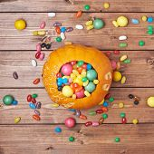 stock photo of foreshortening  - Halloween pumpkin filled with sweets and candies over the wooden board surface - JPG