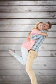 foto of pick up  - Handsome man picking up and hugging his girlfriend against wooden planks - JPG