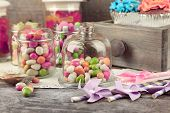 stock photo of sweetie  - Multicolor candies in glass jars and cupcakes on wooden background - JPG