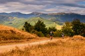 stock photo of dirt-bike  - Two mountain bikers father and son riding mountain bikes in colorful nature - JPG