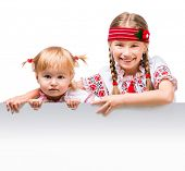 image of national costume  - Two little girls in the Ukrainian national costume stand behind white board with space for text - JPG