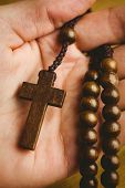 pic of rosary  - Hand holding wooden rosary beads overhead shot - JPG