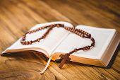 foto of rosary  - Open bible with rosary beads on wooden table - JPG