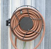 foto of save water  - Water hose for watering the garden outside - JPG