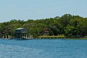 pic of dock  - Wooden boathouse and dock along waterway with coastline and trees - JPG