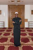 stock photo of muslim man  - African Muslim Man Making Traditional Prayer To God While Wearing A Traditional Cap Dishdasha  - JPG