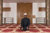 picture of muslim man  - African Muslim Man Making Traditional Prayer To God While Wearing A Traditional Cap Dishdasha - JPG