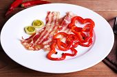 picture of bacon strips  - Strips of bacon with sliced shallot and pepper in plate on wooden table background - JPG