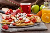 stock photo of maple syrup  - Homemade waffles with maple syrup and strawberries topped cream and chocolate chips orange fresh beverage - JPG