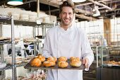 stock photo of trays  - Cheerful baker holding tray of bread at the bakery - JPG