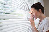 stock photo of peek  - Woman peeking through the blinds from inside - JPG