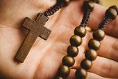 image of rosary  - Hand holding wooden rosary beads in close up - JPG